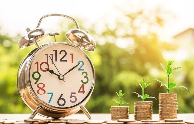 relógio com moedas ao lado para ilustrar o financiamento minha casa minha vida