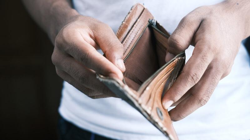 homem com uma carteira na mão para sabe se prefere comprar terreno ou guardar dinheiro
